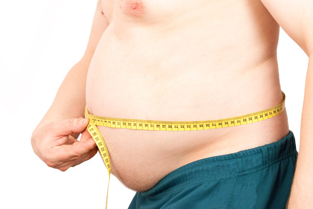 Fat man holding a measurement